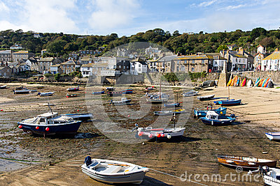 Boats in Mousehole harbour Cornwall England at low tide
