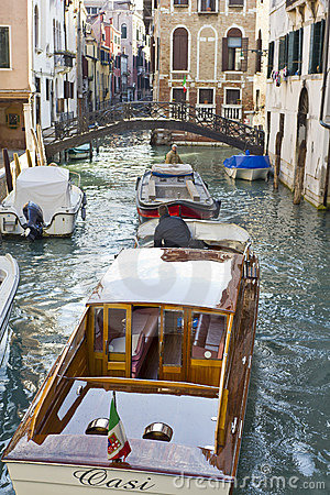 Boats navigating canal in Venice Editorial Photo