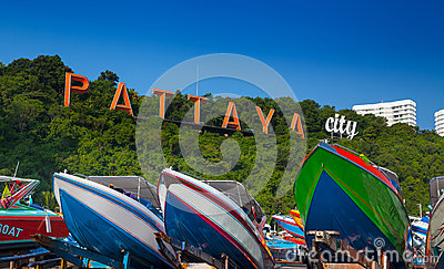 Boats and words Pattaya on the mountain in Pattaya beach, Thailand.