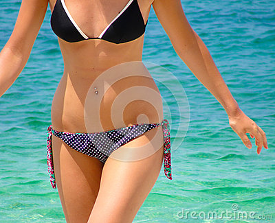 Body of a lady wearing swimming suit on the beach with blue sea