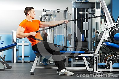 Bodybuilder man doing exercises in fitness club