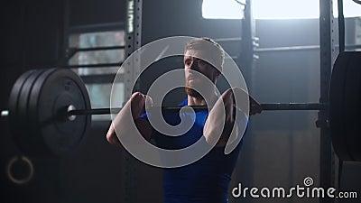 Bodybuilder maschile per fare esercizio con una barra pesante Lunga vita all'uomo che pratica il passaggio a scatto presso un cen video d archivio