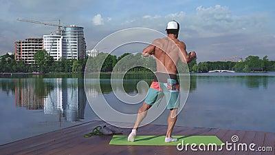 Bodybuilder mentre pone le foto sulla telecamera e mostra il suo corpo forte stock footage