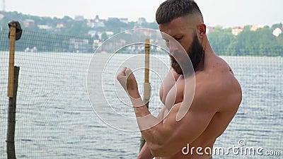 Bodybuilder mostra i muscoli Giovani atletici barbuti che costruiscono il corpo fanno sport all'aperto stock footage