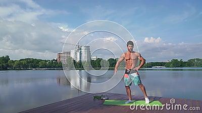 Bodybuilder mostra il suo corpo muscolare a macchina fotografica vicino al lago video d archivio