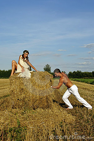 Bodybuilder pushes a haystack with a girl on top