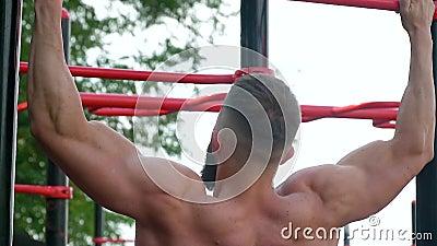 Bodybuilder puxa para cima em uma barra horizontal Jovens carroçarias atléticas barbadas praticam esportes ao ar livre vídeos de arquivo