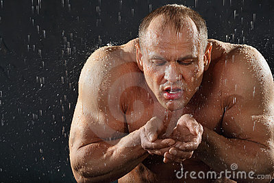 Bodybuilder in rain drinks water from hands