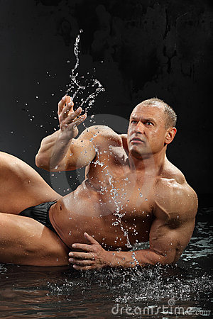 Bodybuilder in rain lies on wet floor