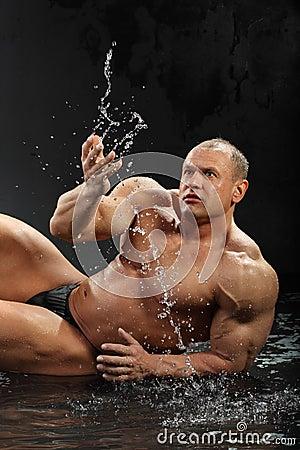 Bodybuilder in rain lies on wet floor