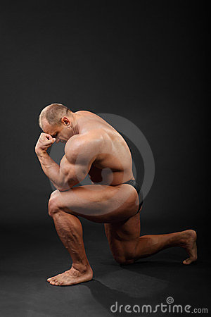 Bodybuilder stands on one knee and thinks