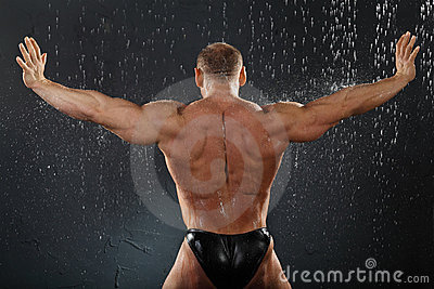 Bodybuilder stands in rain back to camera