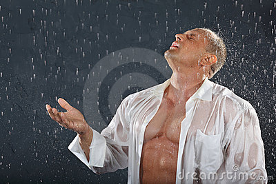 Bodybuilder stands in rain and catches drops