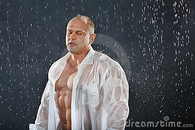 Bodybuilder stands in rain with closed eyes