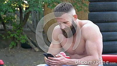 Bodybuilder usa smartphone Jóvenes constructores deportivos con barba juegan deportes al aire libre almacen de video