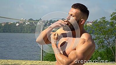 Bodybuilding pali papierosa Młody brodaty kulturysta sportowy gra na wolnym powietrzu zbiory