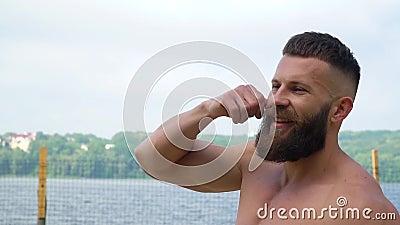 Bodybuilding robi zabawny gest i skręca wąsy Młody brodaty kulturysta sportowy gra na wolnym powietrzu zbiory