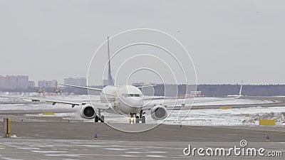 Boeing 737-800 von den mongolischen Fluglinien, die auf Rollbahn, Winteransicht mit einem Taxi fahren stock video