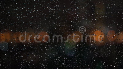 Bokeh through Wet Window. Subject: Rain drop on the window with the bokeh of city in the background. Shot: Bokeh, Blurred Background stock footage