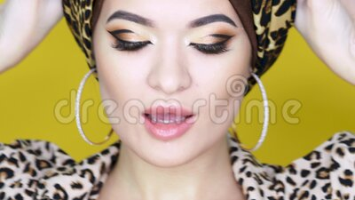 bold and beautiful young woman in a turban with a leopard
