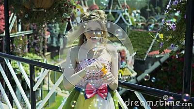 Bolhas de sabão de sopro da mulher loura nova 'sexy' no jardim Consideravelmente sonhar a menina bonito no vestido engraçado do l video estoque