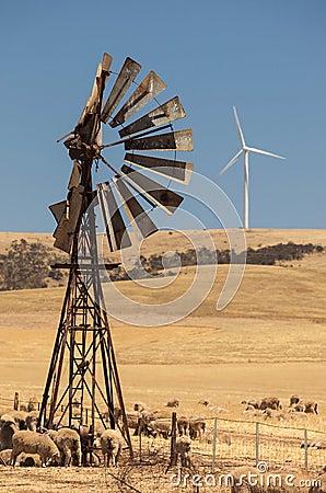 A bomba de vento velha e os geradores de vento novos distorceram pelo ar quente. Sul da Austrália.