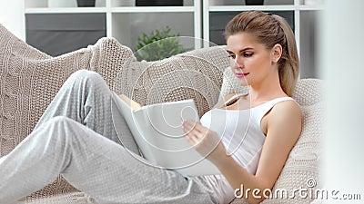 Bonita calma fêmea empalidecida lendo livro em casa confortável e meio-tiro vídeos de arquivo