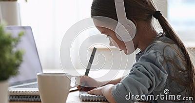 Bonita colegiala de primaria con auriculares aprendiendo a distancia en casa metrajes