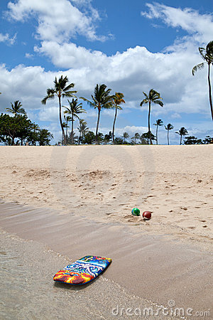 Boogie board and beach balls on a tropical beach