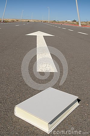 Book and arrow on a asphalt street to the future