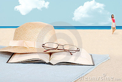 Book glasses and hat on the beach