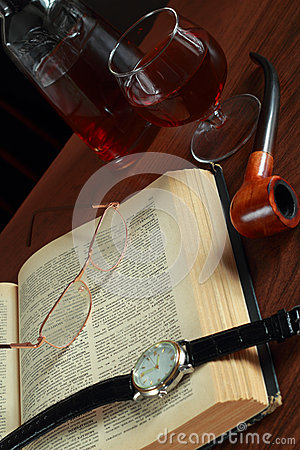Book, glasses, wrist watches and cognac