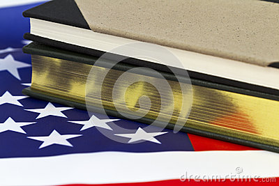 Book with gold pages on American flag