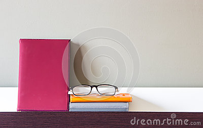 Book, Notebooks and glasses on shelf Stock Photo