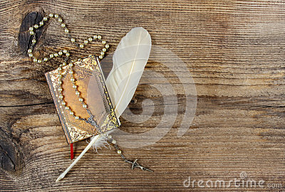 Book, rosary and feather on wood