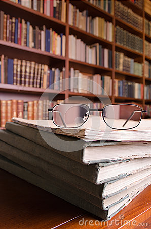 Books and glasses on library table