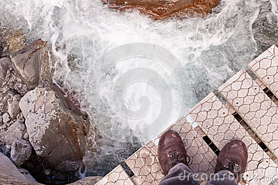 Boots on narrow bridge over troubled white water