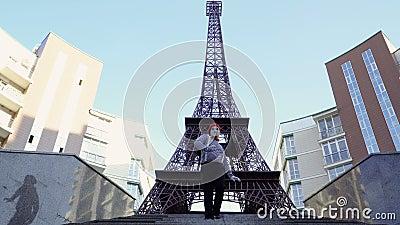 Boots in rode baret na die zich achteruit op trap dichtbij de toren van Eiffel bewegen stock footage