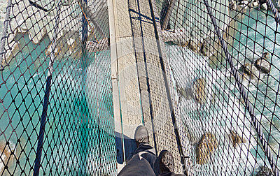 Boots on swing bridge over troubled white water