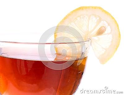 Borde de la taza transparente con té y el limón