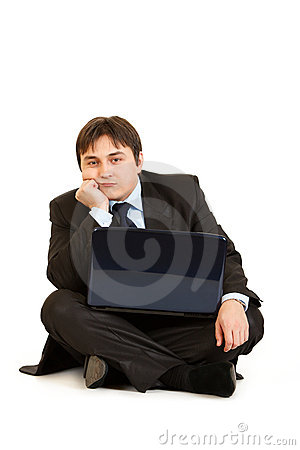 Bored businessman sitting on floor with laptop