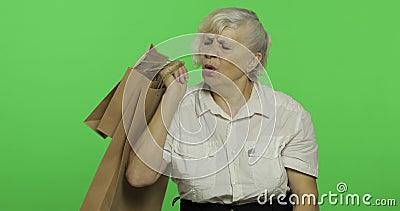 Bored de bejaarden vrouw met het winkelen zakken Het winkelen presents Twee in: 1 stock footage
