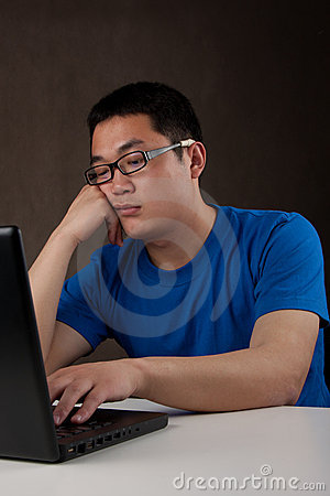 Free Bored Young Asian Man Working With His Computer Stock Image - 19683641