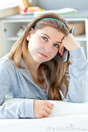 Bored young woman holding a remote in the kitchen
