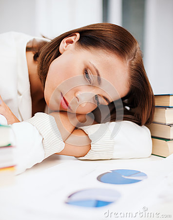 Bored young woman with many books and graphs