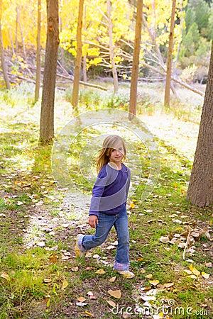 Borrão de movimento running da floresta da árvore de álamo da menina do miúdo do outono