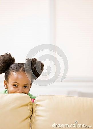 Boshaftes afrikanisches Mädchen, das hinter Sofa sich versteckt