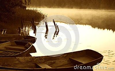 Bosquejo de la madrugada por el lago brumoso con los barcos