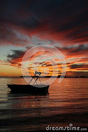 Bote pequeño en la puesta del sol del agua