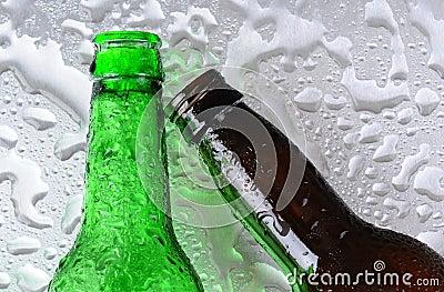 Botellas de cerveza en superficie mojada